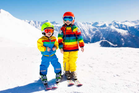 Child skiing in the mountains. Kid in ski school. Winter sport for kids. Family Christmas vacation in the Alps. Children learn downhill skiing. Alpine ski lesson for boy and girl. Outdoor snow fun. Imagens