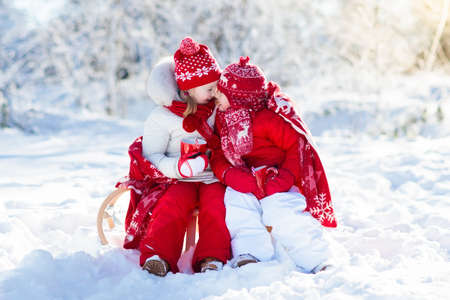Kids sledding in winter forest. Children drink hot chocolate on sled under warm blanket. Boy and girl play in snow on Christmas vacation. Xmas family fun. Kid with cocoa on sledge. Child with sleigh. Banco de Imagens - 90105035
