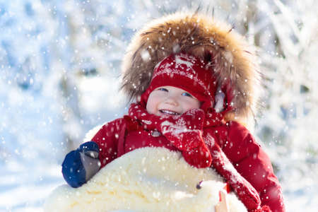 Sled and snow fun for kids. Baby sledding in snowy winter park. Little boy in warm red jacket and knitted hat sitting in sheepskin footmuff. Kid on sleigh. Child on sledge. Family Christmas vacation. Stock Photo