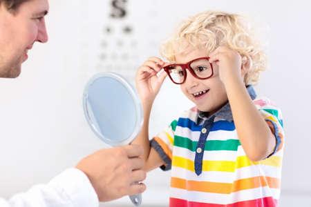 Kind bij gezichtsvermogen test. Weinig jong geitje die glazen selecteren bij opticienopslag. Gezichtsvermogenmeting voor schoolkinderen. Oogbescherming voor kinderen. Arts oogcontrole uitvoeren. Jongen met bril op de briefkaart.
