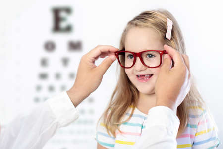 Child at eye sight test. Little kid selecting glasses at optician store. Eyesight measurement for school kids. Eye wear for children. Doctor performing eye check. Girl with spectacles at letter chart. Stock Photo