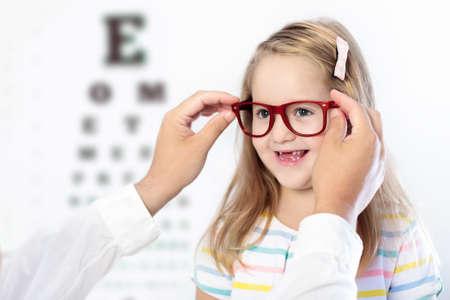 Niño en prueba de vista. Niño que selecciona los vidrios en la tienda óptica. Medición de la vista para niños de la escuela. Ojos para niños. Doctor que realiza la revisión visual. Chica con gafas en el cuadro de carta. Foto de archivo - 90263798