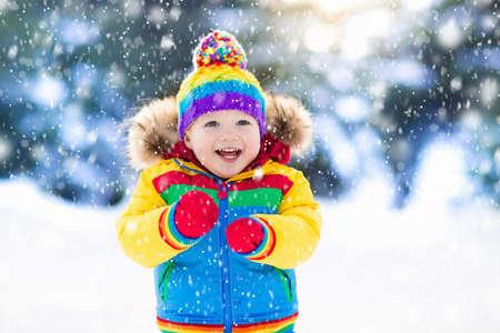 Kind het spelen met sneeuw in de winter. Weinig jongen in kleurrijk jasje en een gebreide hoed die sneeuwvlokken in de winterpark vangen op Kerstmis. Kinderen spelen en springen in besneeuwd bos. Kinderen vangen sneeuwvlokken