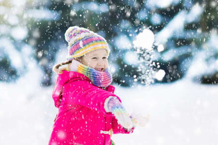 Child playing with snow in winter. Little girl in colorful jacket and knitted hat catching snowflakes in winter park on Christmas. Kids play and jump in snowy forest. Snow ball fight for children.