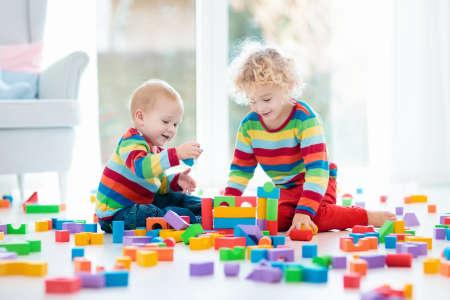 子供たちは、木のおもちゃ積み木で遊ぶ。子供のためのカラフルな玩具。男の子と女の子の大きな窓と、幼稚園の部屋で遊ぶ。子供虹ブロックの塔 写真素材