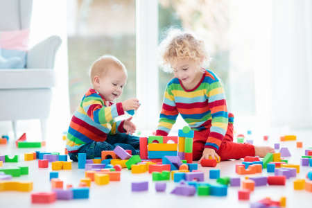 Kids play with wooden toy blocks. Educational colorful toys for children. Boy and girl playing in kindergarten room with big window. Kid building tower with rainbow blocks. Child at home.