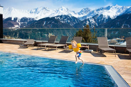 Little child playing in outdoor swimming pool of luxury alpine resort in the Alps mountains, Austria. Winter and snow vacation with kids. Hot tub outdoors with mountain view. Children play and swim.