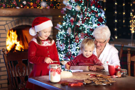 Grandmother and children baking Christmas cookies at fire place and Xmas tree. Kids and grandma bake sweets. Family with kids celebrating Christmas at home. Boy and girl cooking. Generations love. Stock Photo