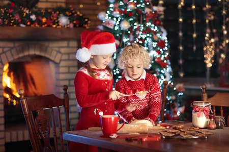 Children baking Christmas cookies at fire place and decorated tree. Kids bake Xmas sweets. Family with kids celebrating Christmas at home. Boy and girl cooking in the kitchen. Winter fun for children Stock Photo