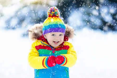 Child playing with snow in winter. Little boy in colorful jacket and knitted hat catching snowflakes in winter park on Christmas. Kids play and jump in snowy forest. Children catch snow flakes Stock Photo