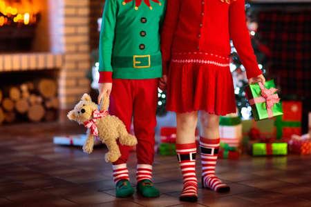 Kinderen bij kerstboom en open haard op kerstavond. Familie met kinderen thuis Kerstmis vieren. Jongen en meisje in bijpassende pyjama kerstboom versieren en openen presenteert. Vakantie geschenken voor kind.