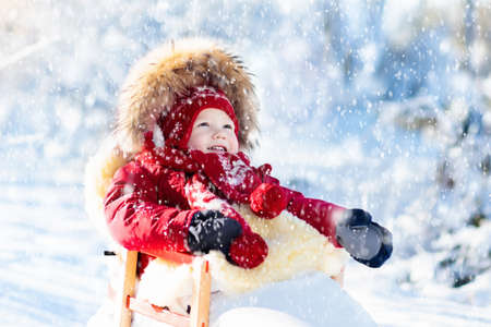 Sled and snow fun for kids. Baby sledding in snowy winter park. Little boy in warm red jacket and knitted hat sitting in sheepskin footmuff. Kid on sleigh. Child on sledge. Family Christmas vacation. Banque d'images