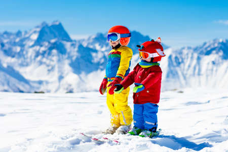 Child skiing in the mountains. Kid in ski school. Winter sport for kids. Family Christmas vacation in the Alps. Children learn downhill skiing. Alpine ski lesson for boy and girl. Outdoor snow fun. Stock Photo