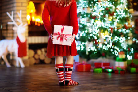 Child at Christmas tree and fireplace on Xmas eve. Little girl holding present box. Child with gift. Family with kids celebrating Christmas at home. Gifts for winter holidays at fire place. Back view. Banque d'images