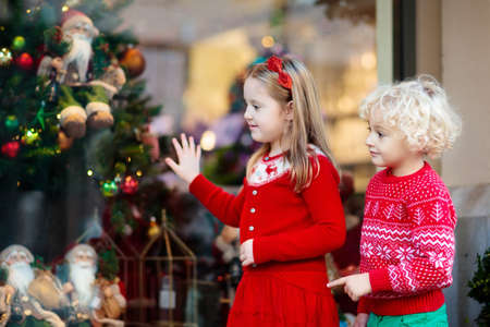 Kids shopping for Christmas presents. Children buy Xmas decoration and tree. Little girl and boy at decorated shop window with lights and Santa toys. Family buying Christmas gifts. Winter holidays. Stock Photo