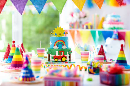 Kids birthday party decoration. Colorful cake with candles. Farm and transportation theme boys party. Decorated table for child birthday celebration. Rainbow cake for little boy. Balloons and banners. Фото со стока
