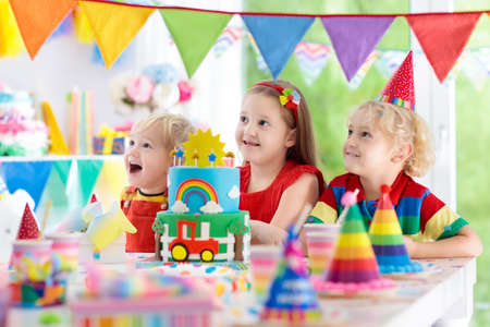 Kids birthday party. Child blowing out candles on colorful cake. Decorated home with rainbow flag banners, balloons, confetti. Farm and transport theme. Little boy celebrating birthday. Party food.