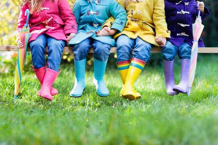 장화에있는 아이들의 그룹입니다. 어린이를위한 다채로운 신발. 소년과 소녀 무지개 wellies 및 duffle 코트. 무지개 발 착용 및 가을 또는 겨울 의류. 비가 스톡 콘텐츠