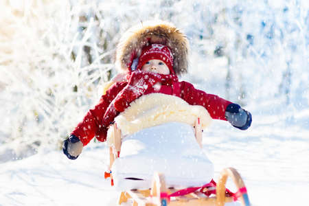 Sled and snow fun for kids. Baby sledding in snowy winter park. Little boy in warm red jacket and knitted hat sitting in sheepskin footmuff. Kid on sleigh. Child on sledge. Family Christmas vacation. Archivio Fotografico