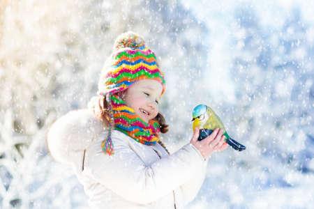 冬の公園で子供が餌を与える。子供たちは雪の森で鳥に餌を与える。ティトマウスを持つ小さな女の子。子供たちは野生動物を見ます。家族のクリ