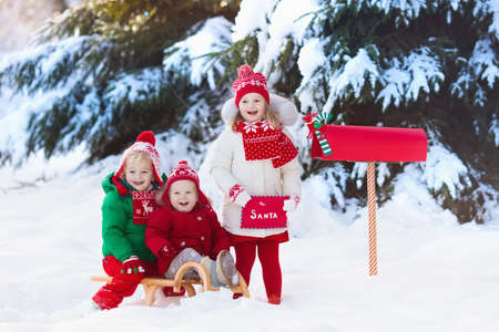 Happy children in knitted reindeer hat and scarf holding letter to Santa with Christmas presents wish list at red mail box in snow under Xmas tree in winter forest. Kids sending post to North Pole. Stok Fotoğraf - 90084255