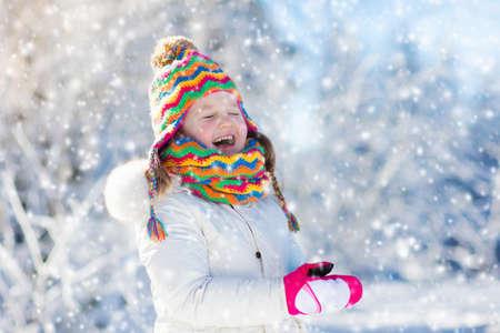 Kind voedende meesvogel in de winterpark. Kinderen voeden vogels in besneeuwde bossen. Meisje met mees. Kinderen kijken naar wilde dieren. Familie Kerstvakantie. Kinderen spelen in de sneeuw. Outdoor- en wildlife-plezier. Stockfoto