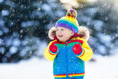 Child playing with snow in winter. Little boy in colorful jacket and knitted hat catching snowflakes in winter park on Christmas. Kids play and jump in snowy forest. Children catch snow flakes Stock fotó