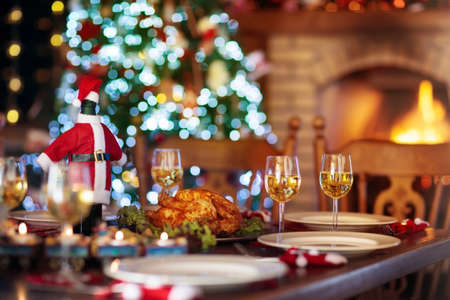 Christmas dinner at fireplace and decorated Xmas tree. Dish with roasted turkey, salad and baked potato served for festive family meal. Wine bottle with Santa hat. Open fire in stone oven.