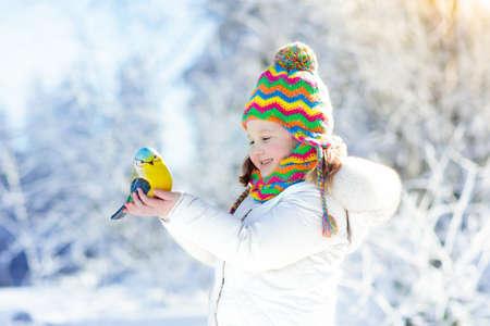 ウィンター パークにシジュウカラの餌の子。子供たちは、雪に覆われた森林の鳥をフィードします。シジュウカラを持つ少女。子供たちは、野生動
