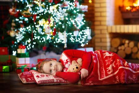 Niño durmiendo en el lugar del fuego en Nochebuena bajo el árbol decorado. Familia celebrando la Navidad en casa. Los niños duermen. Regalos en el lugar del fuego. Niña debajo de la manta en pijamas de las vacaciones de invierno.