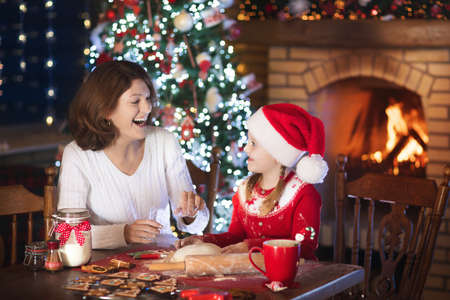 Mother and daughter baking Christmas cookies at fire place and decorated tree. Mom and child bake Xmas sweets. Family with kids celebrating Christmas at home. Little girl cooking in the kitchen. Stock Photo