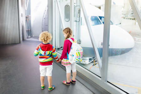 Kids at airport. Children look at airplane. Traveling and flying with child. Family at departure gate. Vacation and travel with young kid. Boy and girl before flight in terminal. Kids fly a plane. Banco de Imagens