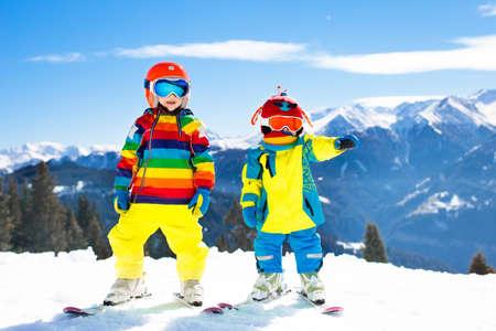 Kinderskifahren in den Bergen. Kid in der Skischule. Wintersport für Kinder. Familienweihnachtsferien in den Alpen. Kinder lernen Abfahrtslauf. Alpinski-Unterricht für Jungen und Mädchen. Schneespaß im Freien.