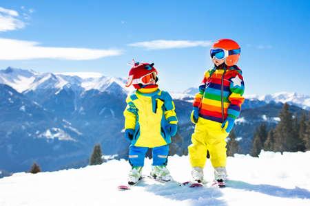 어린이 산속에 스키. 스키 학교에서 키드. 아이들을위한 겨울 스포츠. 알프스에서 가족 크리스마스 휴가입니다. 아이들은 내리막 길을 배웁니다. 소년 스톡 콘텐츠