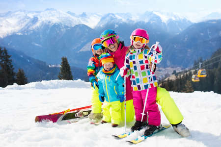 Family ski vacation. Group of young skiers in the Alps mountains. Mother and children skiing in winter. Parents teach kids alpine downhill skiing. Ski gear and eye wear, safe helmets. Snow sports fun.