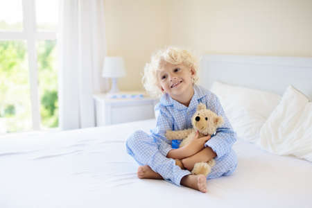 Kids playing in parents bed. Children wake up in sunny white bedroom. Little boy in bllue pajamas. Sleepwear and bedding for child and baby. Nursery interior for toddler kid. Family morning. Stock Photo