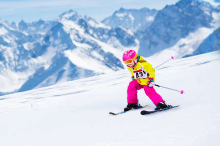 Child skiing in mountains. Active toddler kid with safety helmet, goggles and poles. Ski race for young children. Winter sport for family. Kids ski lesson in alpine school. Little skier racing in snow Archivio Fotografico
