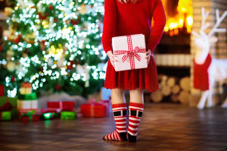 Child at Christmas tree and fireplace on Xmas eve. Little girl holding present box. Child with gift. Family with kids celebrating Christmas at home. Gifts for winter holidays at fire place. Back view. Stock Photo