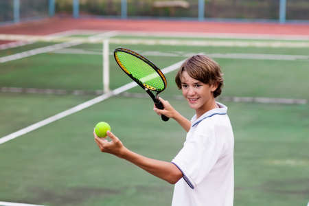 Boy playing tennis on outdoor court. Teenager with tennis racket and ball in sport club. Active exercise for kids. Summer activities for children. Training for young kid. Child learning to play. Stockfoto
