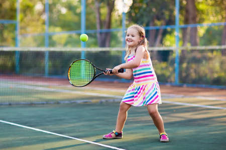 야외 법원에 테니스 선수입니다. 어린 소녀 테니스 라켓 및 스포츠 클럽에서 공을. 아이들을위한 적극적인 운동. 어린이를위한 여름 활동. 어린 아이를