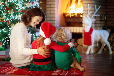 Family with kids at Christmas tree and fireplace. Mother and children opening gifts at fire place. Boy, girl and mom open presents. Winter holidays interior decoration. Child in pajamas on Xmas eve.