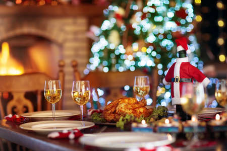 暖炉と装飾されたクリスマスの木でのクリスマスディナー。ロースト七面鳥、サラダ、焼き芋を添えた料理は、お祝いの家族の食事のために提供さ