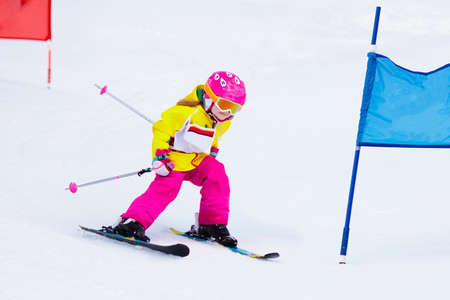 Child skiing in mountains. Active toddler kid with safety helmet, goggles and poles. Ski race for young children. Winter sport for family. Kids ski lesson in alpine school. Little skier racing in snow Stockfoto
