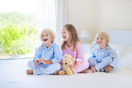 Kids playing in parents bed. Children wake up in sunny white bedroom. Boy and girl play in matching pajamas. Sleepwear and bedding for child and baby. Nursery interior for toddler kid. Family morning.