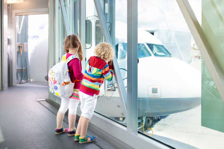 Kids at airport. Children look at airplane. Traveling and flying with child. Family at departure gate. Vacation and travel with young kid. Boy and girl before flight in terminal. Kids fly a plane. Zdjęcie Seryjne
