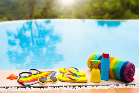 Swimming pool accessories flat lay. Top view of beach items on pool deck. Flip flops, bikini and hat, sun glasses. Water toys. Summer vacation in tropical resort. Copy space. Colorful beach wear. Stock Photo