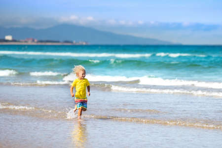 Child on beautiful beach. Little boy running and jumping at sea shore. Ocean vacation with kid. Children play on summer beach. Water fun. Kids run and swim. Family holiday on tropical island.