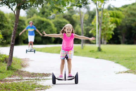 Child on hover board. Kids riding scooter in summer park. Balance board for children. Electric self balancing scooter on city street. Girl learning to ride hoverboard. Modern gadgets for school kid. Stock Photo - 91543778
