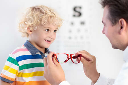 Child at eye sight test. Little kid selecting glasses at optician store. Eyesight measurement for school kids. Eye wear for children. Doctor performing eye check. Boy with spectacles at letter chart. Banco de Imagens