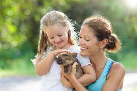 Crianças brincam com animais de fazenda. Alimentação infantil animal doméstico. Mãe nova e menina que guardam o bebê do javali no jardim zoológico petting. Criança brincando com porco recém-nascido. Crianças e animais de estimação. Família em férias de fazenda Foto de archivo - 92123833